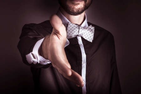 the etiquette: Cropped torso portrait of a polite fashionable sophisticated man wearing a dinner jacket and bow tie offering his hand in an act of chivalry or greeting Stock Photo