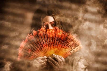 psiquico: Mujer del fuego místico sostiene un abanico oriental quema en una neblina smokey de misterio y magia. psíquica clarividente