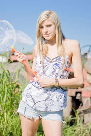 ambush: A Woman With A Playful Look Stands Ready To Pounce With A Butterfly Net In Hand While On A Bush Ambush