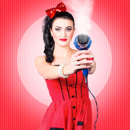 drying: Portrait of a young beautiful pinup girl taking aim with hair dryer over retro red background. Hair care concept Stock Photo