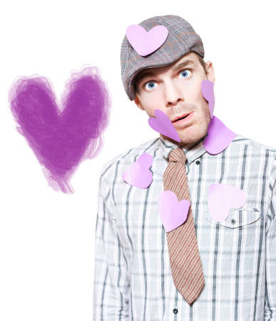 lovelorn: Portrait Of A Cute Young Boy In Love Standing In Front Of Purple Heart Illustration Drawn On The Wall On White Background