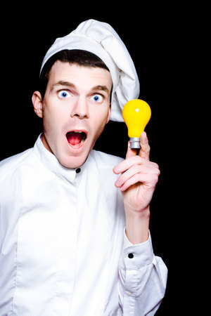 ideas: Chef With A Great Idea For A Winning Recipe Holding Up A Conceptual Yellow Light Bulb With A Look Of Excited Surprise At His New Found Culinary Invention Stock Photo