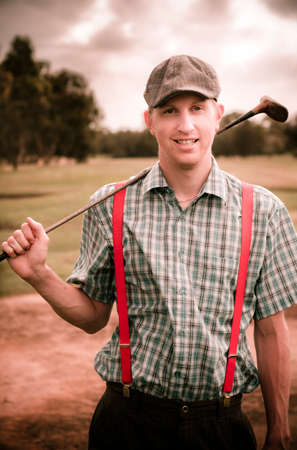 bygone: Smiling Classic Retro Golfer Wearing Flat Cap And Suspenders Holds His Golf Club Over His Shoulder On A Bygone Golfing Fairway Of Yesteryear