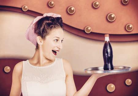 Klassisches Portrait eines Retro-Pinup Mädchen mit Essen und Trinken Schale mit Soft-Drink-Flasche im Inneren vintage Cafeteria. 50s Diner Rückblende