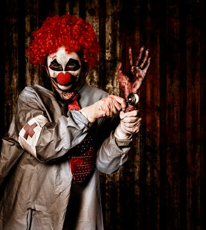 Monster medical clown checking the pulse on a rotten severed human hand with stethoscope. Black market limbs