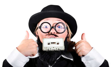 bowler hat: Person With Bowler Hat And Nerd Glasses Holding Cassette In Mouth With Showing Thumb Up Sign