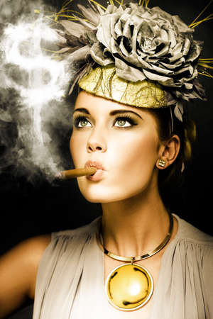 snob: Wealthy woman in haute couture and ostentatious jewellery smoking a big fat cigar, conceptual of wealth and riches