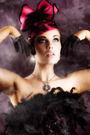 music hall: Beautiful dancer with pink hat and black feather dress performing an exotic cancan dance in a smokey music hall Stock Photo