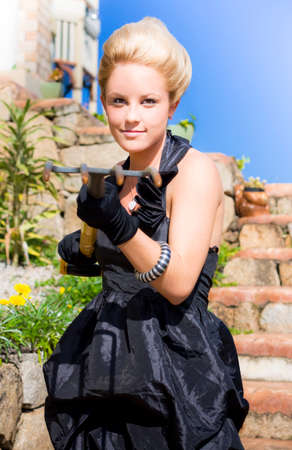 half dressed: Half Body Portrait Of Fashionable Young Blond Woman With Gardening Fork In Hands; Dressed To Kill Concept