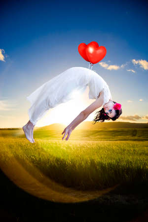 lightness: In A Flight Of Fancy A Pretty Woman Floats In An Air Of Love And Happiness Held Up By Two Red Love Heart Shaped Balloons In A Image Depicting Love Romance And Joy Stock Photo
