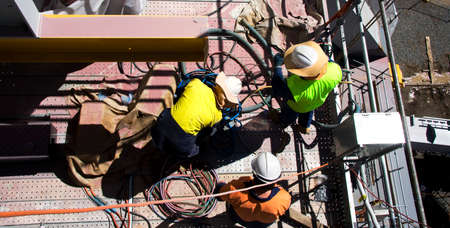 Three Construction Site Workers Wrap And Sort Electrical Cables Stock Photo
