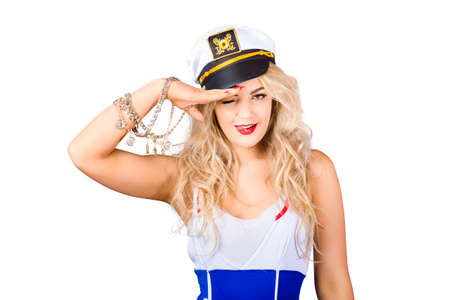 Quirky portrait of young beautiful sexy sailor girl with blond wavy hair and stylish make-up wearing sea admirals hat. Eye eye captain Stock Photo