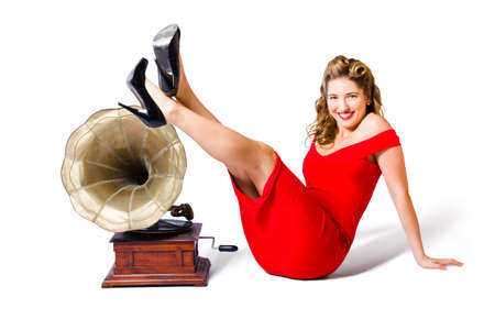 phonograph: Isolated photograph of a pretty and young pinup girl in rockabilly dress kicking up a pose next to antique record player in a musical depiction of classical music