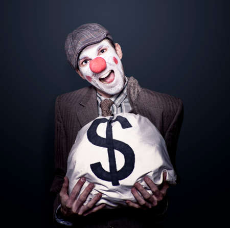 bank robber: Dodgy Bank Robber Clown Holding Dollar Sign Money Bag While Laughing Out Loud In A Depiction Of Funny Money