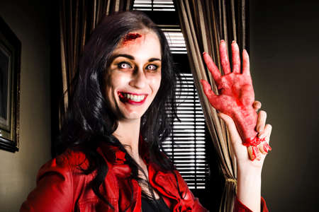 reanimated: Demon like female businessperson waving hello inside a corporate office with sawn off hand in a depiction of untrustworthy business partnerships