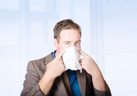 cold season: Unwell male office worker suffering from a contagious virus, covering face with tissue during cold and flu season