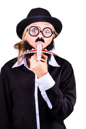 specs: Funny blond woman in black  dress , black hat and thick rimmed black spectacles eating a toy plane on white background