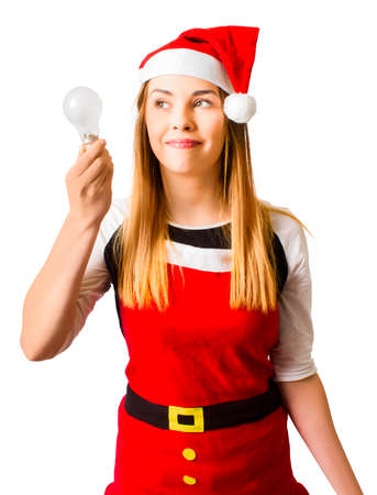 creatively: Isolated picture of a attractive girl in 20s holding lightbulb decoration in x-mas costume while thinking creatively. In light of christmas ideas