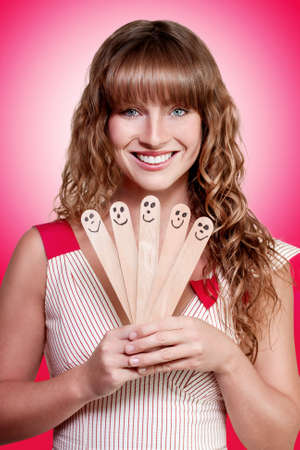 splayed: Happy smiling attractive businesswoman presenting her successful business team consisting of five wooden tongue depressors with smiling faces in a humorous Happy Business Team concept
