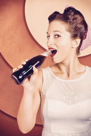 french roll: Retro pin up pop art of a cool girl from 1950 standing in vintage cafeteria drinking from old soda bottle with French roll hairdo and red lip cosmetics Stock Photo
