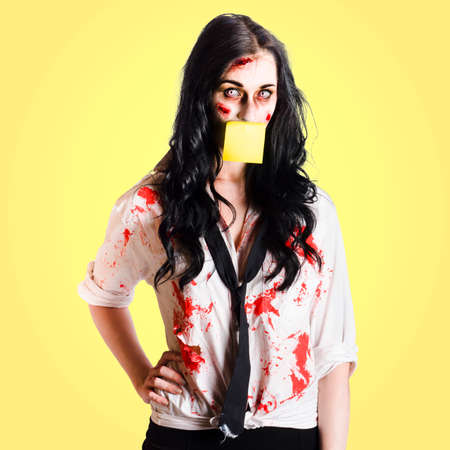 reanimated: Tired overworked and stressed business woman in decay wearing sticky note to-do list on face Stock Photo