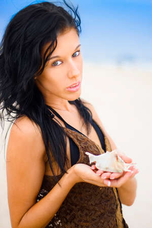 solicitous: Attractive Young Female Holding Seashell With Expression Of Care As If Expressing Her Environmental Concern For Preserving The Natural Beach Environment And Protecting It From Pollution Stock Photo