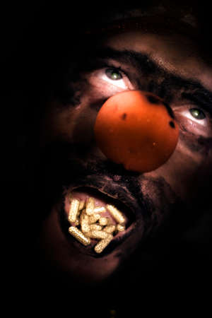 shadowed: Closeup Of A Clowns Shadowed Face With His Mouth Full Of Capsules In Dose Of Laughter Concept