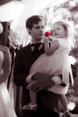 flowergirl: A Young Handsome Father Wearing A Tuxedo Holding His Beautiful Two-Year-Old Daughter In His Arms And Looking At Her With Love And Concern For Her Future