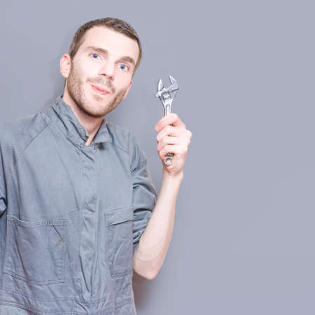 boiler suit: Smiling Young Male Mechanic In Boiler Suit Holding Wrench Against A Grey Copyspace Background Stock Photo