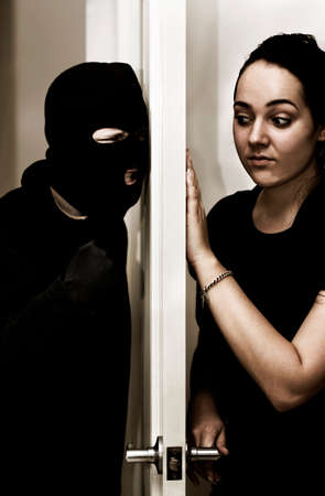 intruder: A Violent Intruder Bashes On A Door While A Female Occupant Hesitantly Opens Up Stock Photo