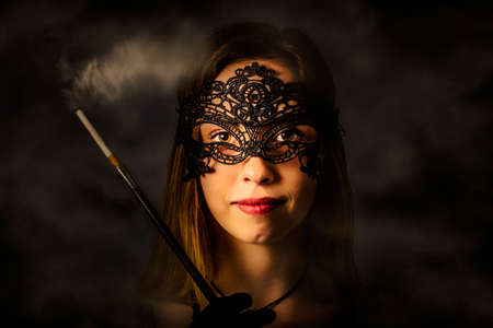 masquerader: Vintage horizontal photo on a young beautiful girl holding cigarette in the darkness of a new years eve mask party. Classical masquerader Stock Photo