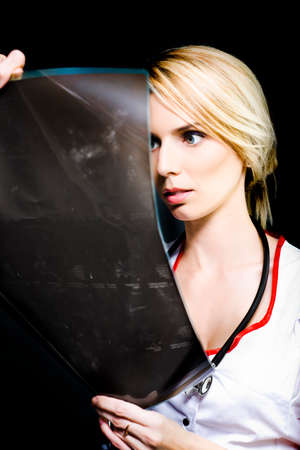 disbelief: Beautiful blonde female doctor or radiologist holding up an x-ray film with a wide-eyed expression of shock, horror and disbelief at what she is seeing