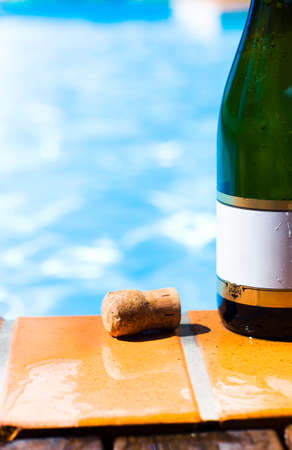 rimmed: Green champagne bottle with a blank gold rimmed label and a cork standing on wet tiles alongside a sparkling blue swimming pool in a summer party concept