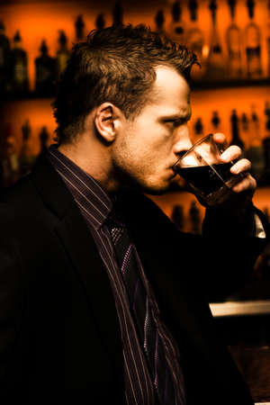 intoxicant: Rough And Tough Serious Male Drinker Downing A Glass Of Alcoholic Beverage Standing In Front Of A Bar In A Depiction Of Hard Stuff Stock Photo