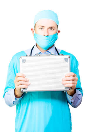 organ donation: Conceptual image of a young male surgeon in a mask and gown holding up a small metal case signifying an organ donation or transplant