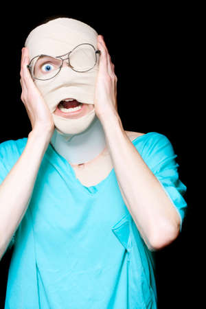 anguished: Scared Medical Patient Wrapped In Bandages Shouting Out In Horror In A Depiction Of Accident Trauma On Dark Background Stock Photo