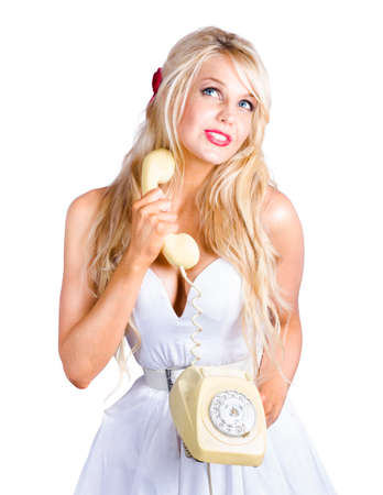 corded: Blonde woman looking up to communication copy space with old-fashion rotary telephone held in hand Stock Photo