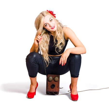 tacones rojos: M�s de blanco retrato de una joven rubia atractiva pin up modelo con tacones rojos escuchar la conversaci�n en el tel�fono viejo. Operador de la central telef�nica Foto de archivo