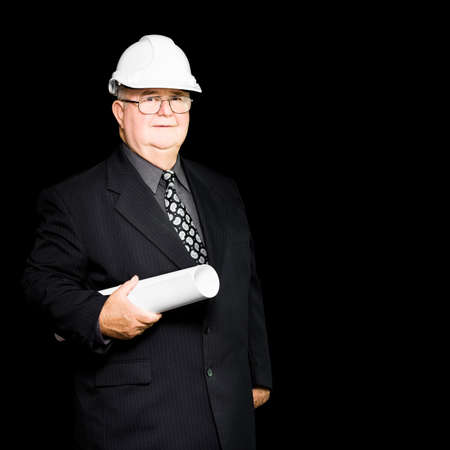 architectural firm: Senior architect in an architectural firm with all the expertise and knowledge of his years carries a blueprint as he goes about a building site inspection Stock Photo