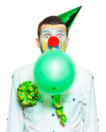 birthday clown: Isolated Birthday Clown In Party Costume, Looking Surprised.While Blowing Up Green Balloon Over White Background