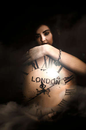 dimly: Woman Standing In Shadows Behind The Face Of A Large Antique Clock Set To London Greenwich Mean Time