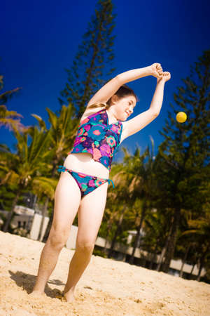 ball stretching: Young girl in her swimming cotume stretching her hands up in the air while playing ball on a sandy beach in summertime Stock Photo