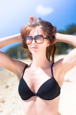 hands on head: Half Body Portrait Of Young Woman Relaxing On Beach With Sunglasses And Bikini Top With Blue Sky Background