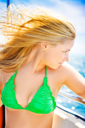 tresses: Beautiful young blonde female tourist with her hair blowing in the ocean breeze looking out over the sea on a travel cruise Stock Photo