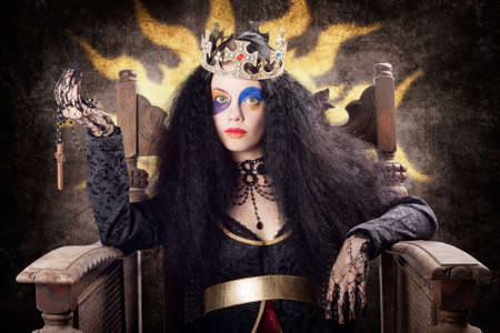 fanatical: Storybook queen jester wearing gold crown and bright make-up holding religious cross on old wooden throne