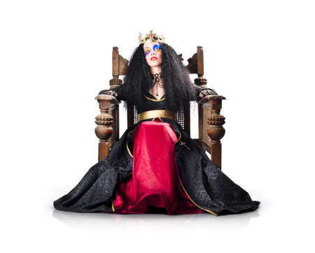 reign: Woman dressed as fantasy queen on wooden throne with crown, white background