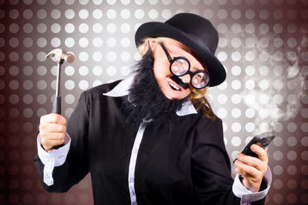 smashing: Frustrated business man smashing a smart mobile phone with hammer in a technology failure concept