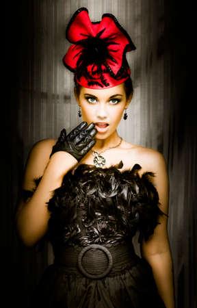 mooie vrouwen: Mooi jong meisje in een zwarte veer cabaret outfit die zich met haar hand omhoog om haar open mond met een geschokt en verrast meningsuiting
