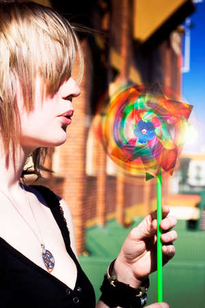 blond haired: Side Portrait Of Young Blond Haired Woman Blowing Rotating Colorful Windmill Toy Outdoors