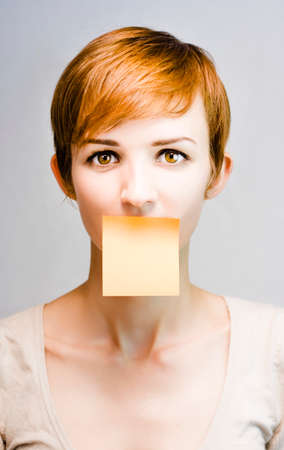 astounded: short-haired girl with blank sticky note stuck to her lips on grey background in a copyspace personal message concept